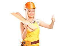Female carpenter holding a couple of planks and giving thumb up Stock Photo