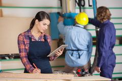 Female Carpenter Holding Digital Tablet In Royalty Free Stock Photo