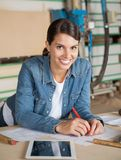 Female Carpenter Leaning On Table In Workshop Stock Images