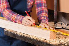 Female Carpenter Marking Wood With Pencil Royalty Free Stock Photo