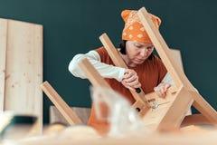 Female carpenter repairing wooden chair seat in workshop royalty free stock photos