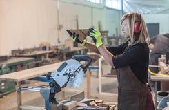 Female carpenter Using Circular Saw. For wood Stock Image