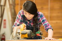 Female carpenter using circular Saw. Carpenter using circular Saw. female woodworker holding circular table electric saw cutting wood in workshop. mixed race Stock Photo
