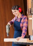 Female Carpenter Using Drill Machine On Wood Stock Image