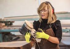 Female carpenter Using Electric Sander Stock Images