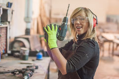 Female carpenter using power drill Royalty Free Stock Photography