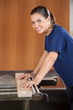 Female Carpenter Using Tablesaw In Workshop Royalty Free Stock Image