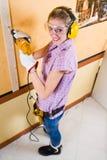 Female carpenter  at work using hand drilling machine Stock Image