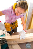Female carpenter  at work using hand drilling machine. A Female carpenter  at work using hand drilling machine Royalty Free Stock Photo
