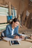 Female Carpenter Working On Blueprint In Workshop Stock Images