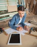 Female Carpenter Working On Blueprint In Workshop Royalty Free Stock Photography