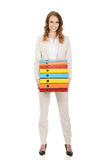 Female carrying heavy binders against. Stock Image