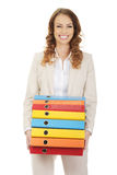 Female carrying heavy binders against. Stock Photography