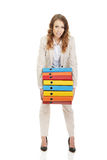 Female carrying heavy binders against. Royalty Free Stock Photo