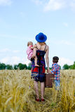 Female carrying valize with two children standing Stock Images