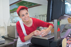 Female cashier at sales desk butcher Royalty Free Stock Photo