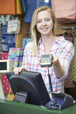 Female Cashier At Sales Desk With Credit Card Machine Royalty Free Stock Images