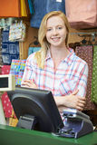Female Cashier At Sales Desk Of Store stock photography