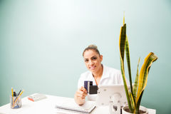 Female cashier swiping a credit card. Portrait of a female cashier at a business front desk swiping a credit card in a reader and smiling Stock Photo