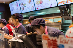 Female cashier working in KFC restaurant