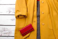 Female cashmere overcoat of yellow color. Women classy topcoat and red purse on wooden background close up Stock Image