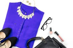 Female casual office style clothing and accessories -purple shirt, heeled shoes, handbag, make up items. Copy space royalty free stock photos