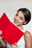Female in casual outfit holding red book. Vertical natural light indoors portrait of young attractive brown-eyed brunette caucasian female in white casual Stock Photography