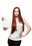 Female in casual outfit holding sign. Vertical studio portrait of young attractive green-eyed caucasian female with long natural straight red hair which holding Royalty Free Stock Photography