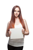 Female in casual outfit holding sign. Vertical studio portrait of young attractive green-eyed caucasian female with long natural straight red hair which holding royalty free stock images