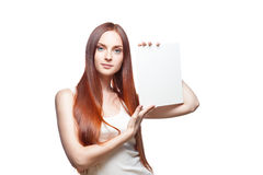 Female in casual outfit holding sign. Vertical studio portrait of young attractive green-eyed caucasian female with long natural straight red hair which holding stock photography