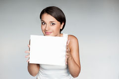 Female in casual outfit holding sign. Horizontal natural light portrait of young attractive briwn-eyed caucasian female with dark hair which dressed in casual Stock Images