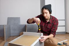 Woman assembling a chest drawer for new bedroom furniture. stock photography