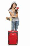 Female in casual standing with travel suitcase. Full length of young female in casual standing with travel suitcase, holding passport and tickets, and showing Royalty Free Stock Photography