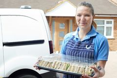 Female Caterer Delivering Tray Of Sandwiches To House. Female Caterer Delivers Tray Of Sandwiches To House royalty free stock photography