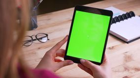 Female caucasian hands holding vertically tablet with green chroma screen on office background. Female caucasian hands holding vertically tablet with green stock video footage
