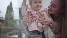 Female Caucasian hands taking little blond girl up. Cute child touching head and smiling as mother talking to the kid stock footage