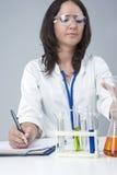 Female Caucasian Laboratory Staff Researching Liquids in Lab Glassware Royalty Free Stock Photos