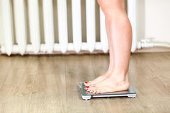 Female Caucasian legs standing on weight scales Royalty Free Stock Photo
