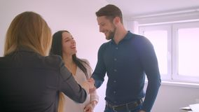 Female caucasian real-estate agent giving the keys from new home to happy young excited couple. Female caucasian real-estate agent giving the keys from new home stock video
