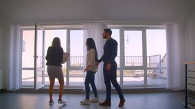 Female caucasian real-estate agent showing the apartment to young caucasian couple invites to watch at the terrace.
