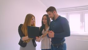 Female caucasian real-estate agent showing and describing the apartment to young caucasian couple. Female caucasian real-estate agent showing and describing the stock footage