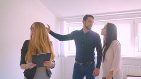 Female caucasian realtor showing and describing the apartment to her young caucasian clients. Female caucasian realtor showing and describing the apartment to stock video footage