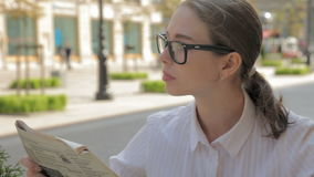 Female caucasian student in outdoor cafe with newspaper. Drinks coffee and reading news stock footage