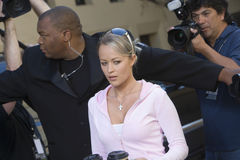 Female Celebrity With Bodyguard And Paparazzi Stock Images