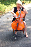 Female cellist. Female cellist with her cello outside royalty free stock photography