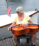 Female cellist outdoors. Mature female cellist with her instrument by the lake royalty free stock image