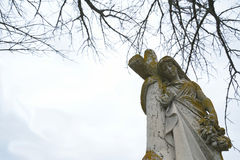 Female cemetery statue leaning on cross and holding wreath Stock Images