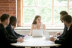 Female CEO explaining business strategy to male subordinates. Female CEO explaining company strategy to male colleagues. Work team analyzing financial rates on Stock Images