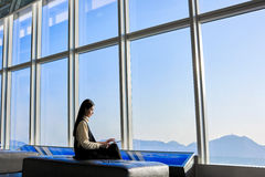 Female CEO is searching information via touch pad, while sitting in office interior against big window with cityscape view Stock Image