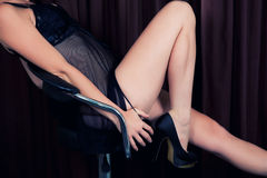 Female on chair in black lingerie in erotic pose Royalty Free Stock Photos